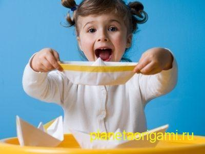 Девочка держит бумажный кораблик