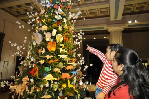 Женщина с ребенком стоят около новогодней елки