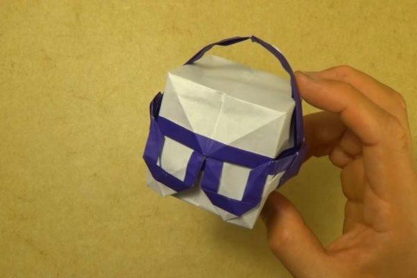 Оригами куб в наушниках из бумаги белого и фиолетового цветов